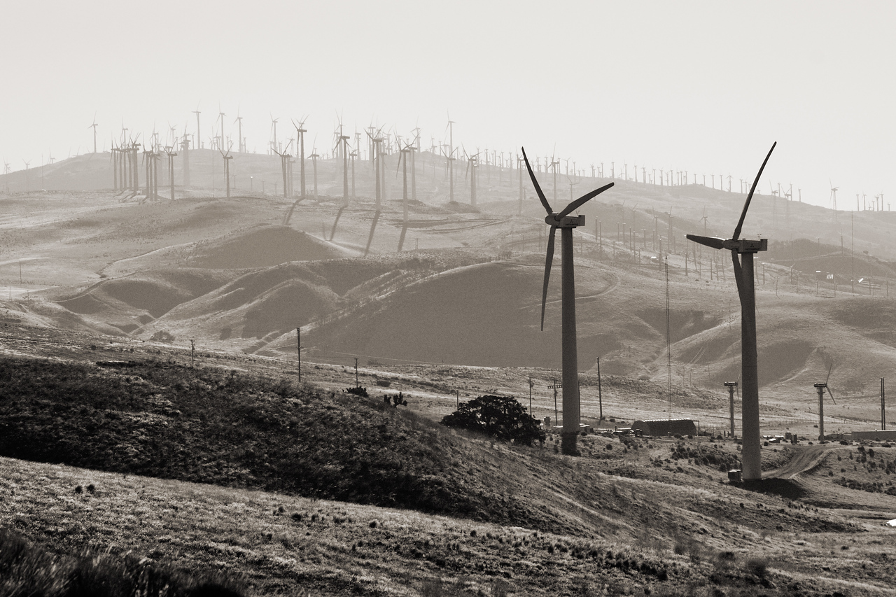 Windmills viewed from the Tehachapi-Willow Springs road.  Heavy summer haze limited visibility but added depth perspective to this shot.  Summer haze in the desert is mostly due to dry hot air carrying dust particles but other sources include salt and pollution spilling over mountain passes.
