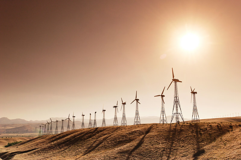 A row of windmills with the sun as a backdrop.  Solar and wind power are underutilized energy sources.  Improvement in technology is necessary to increase the efficiency in which solar and wind power can be harnessed.  This image was taken through a Cokin X124 Tobacco-toned graduated filter.