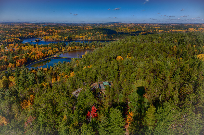 View from Temagami Tower. HDR efx dark. Single red tree near shadow of tower. Looking towards lagoons.