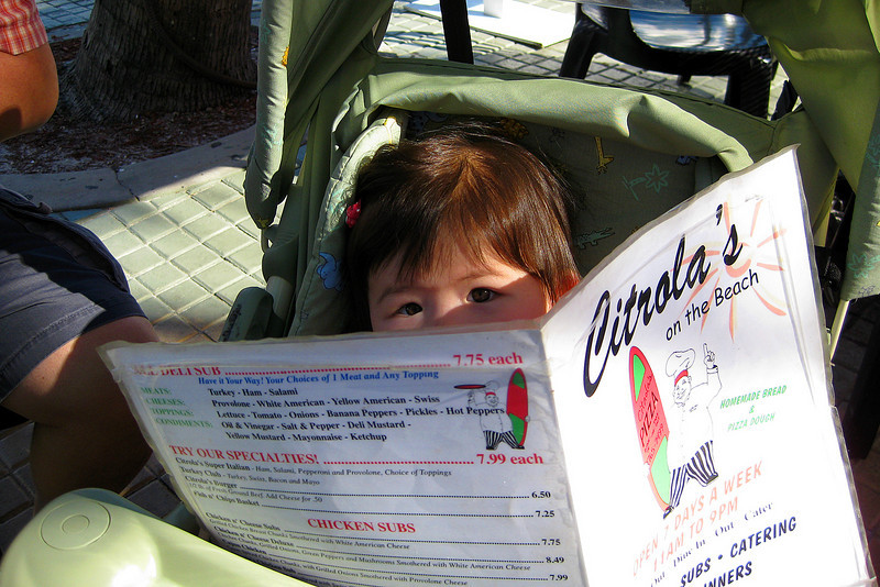 Julia looking at the menu at Citrolas On The Beach restaurant in Fort Myers Beach