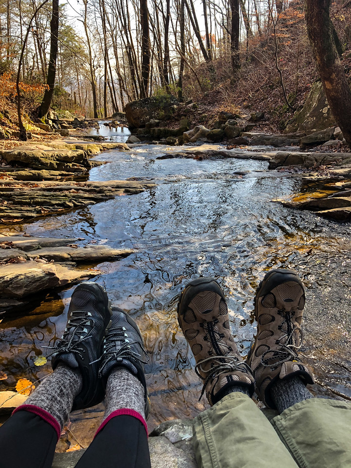 Feet resting on a rock looking over a creek.