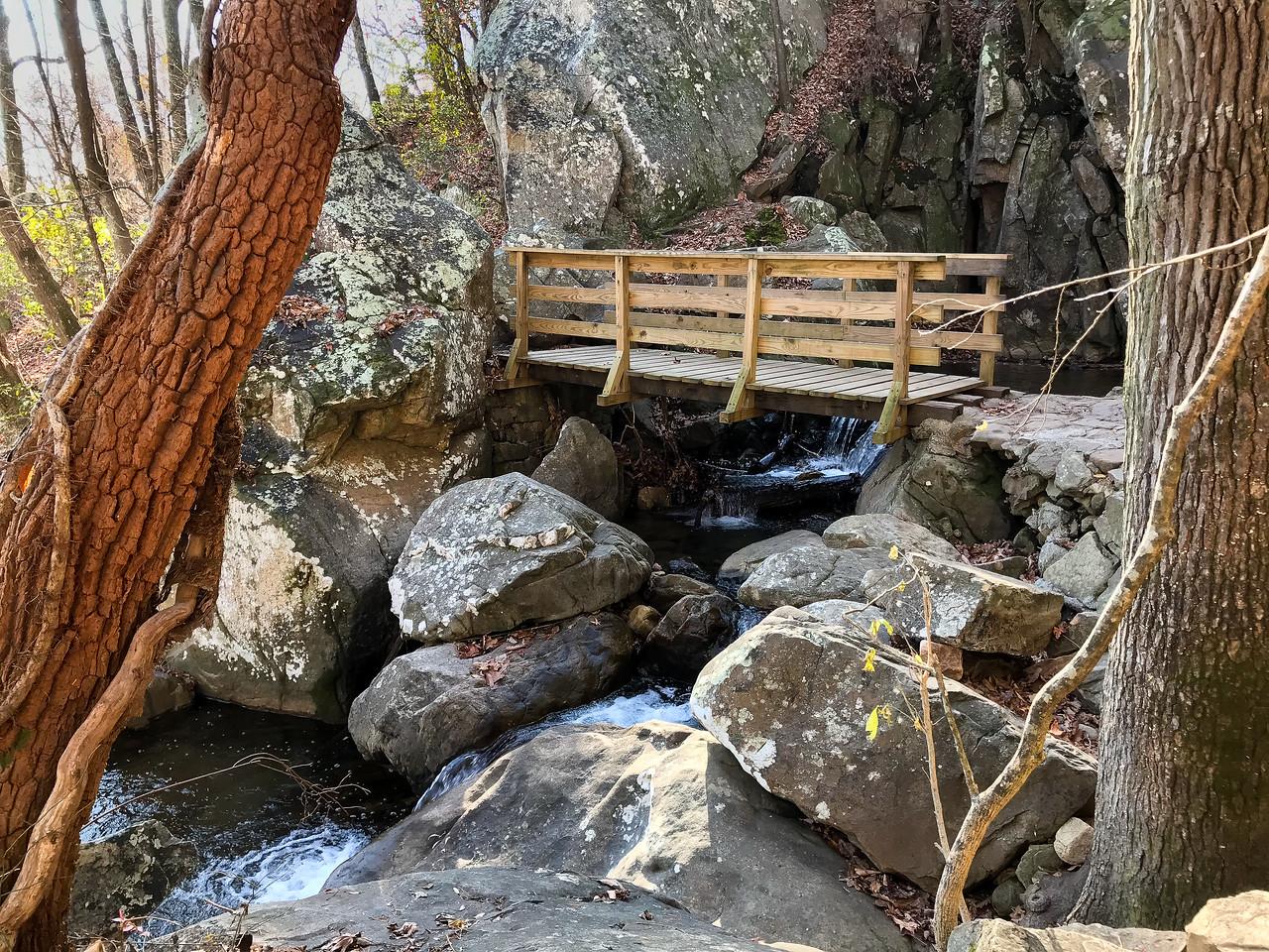 Wooden bridge crossing over falls.