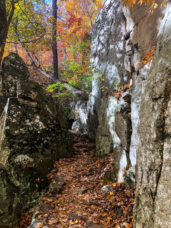 Trail cutting through large boulders.