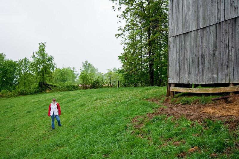 Jennifer on slope by barn and mushroom