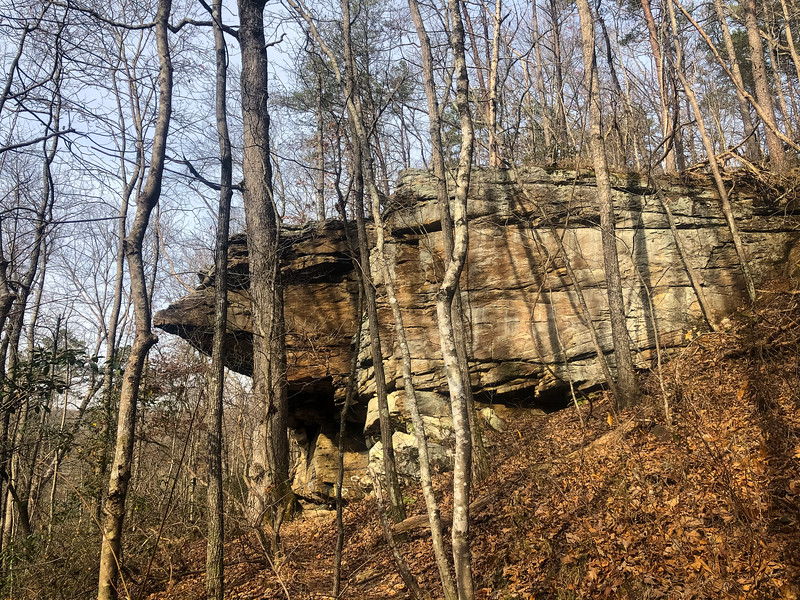 The hiking trail passes under a huge, rocky bluff.