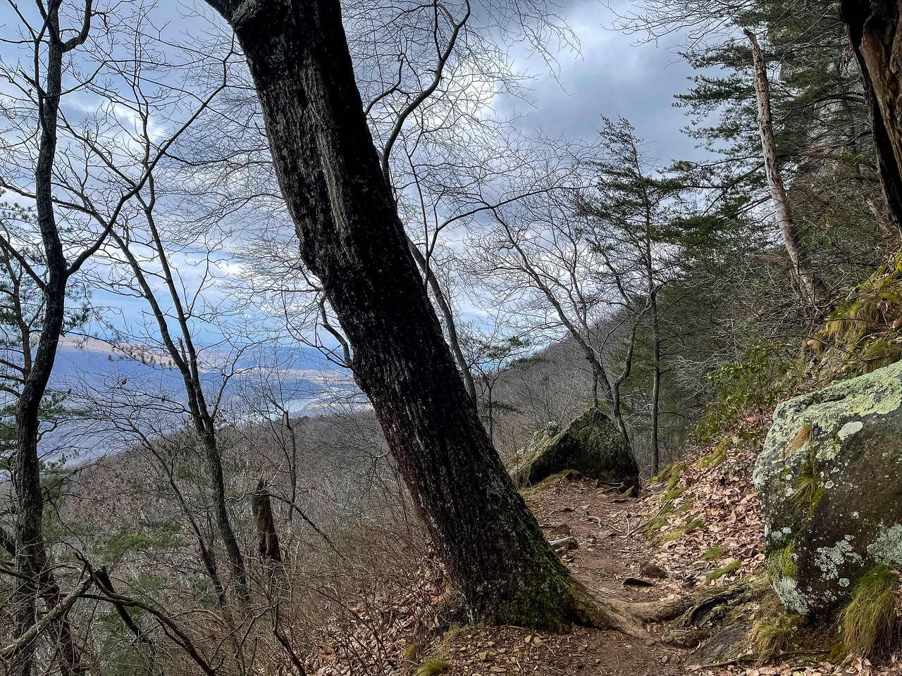 The trail narrows on the bluff with a view of the river and mountains in the distance.