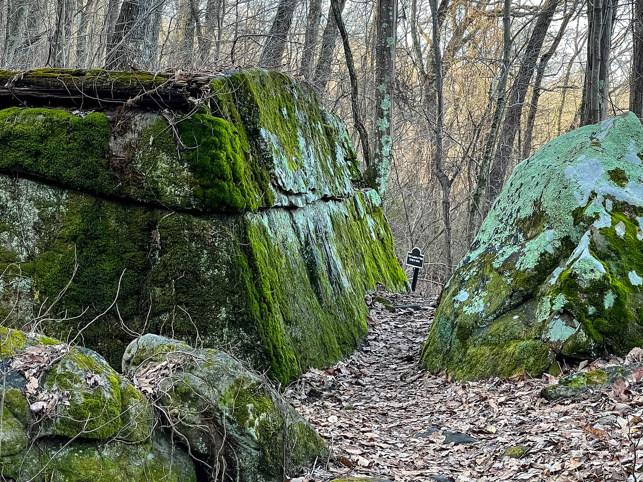 The trail passing between two huge, mossy boulders.