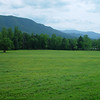 An open field with mountains in the background in Cades Cove in the Great Smoky Mountains National Park.