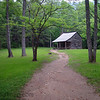 A dirt trail leading to a rustic settlers cabin in the Great Smoky Mountains National Park.