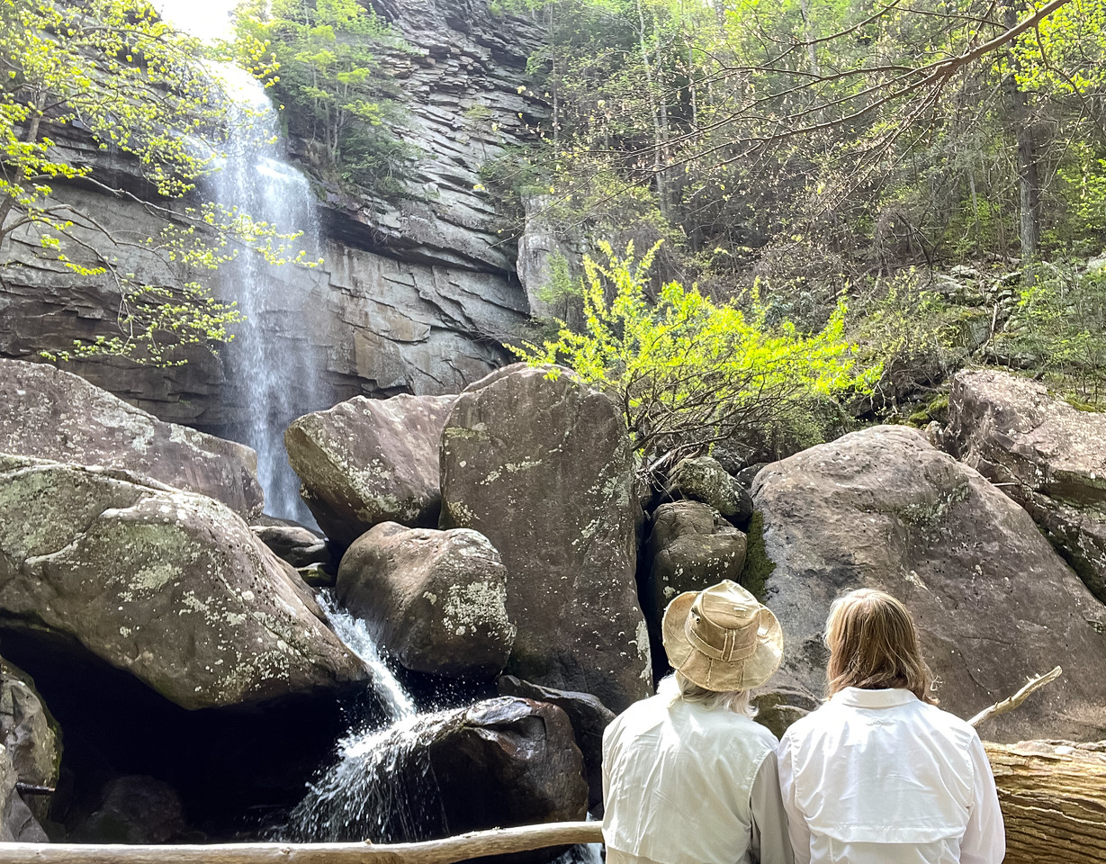 A couple are sitting together on the rocks, looking at Laurel Falls.