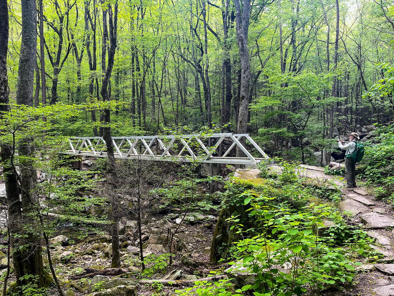 A large metal bridge crossing a creek.