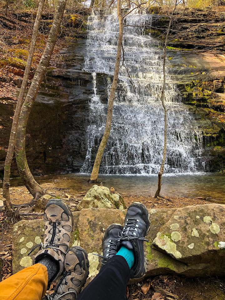 Waterfall with two people's feet.