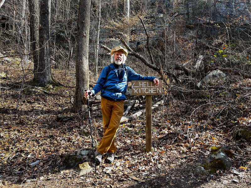 A man stands beside a sign on the trail.