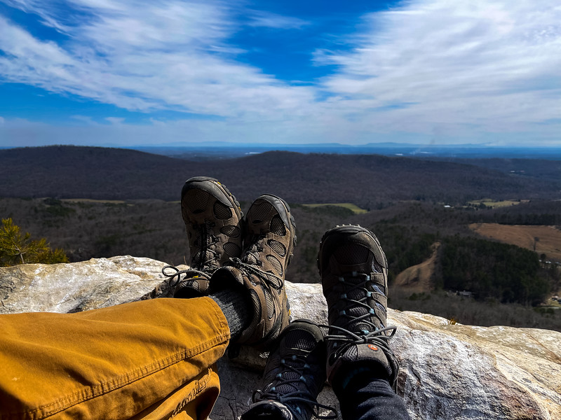 Point of view photo of two people sitting on a rocky overlook.