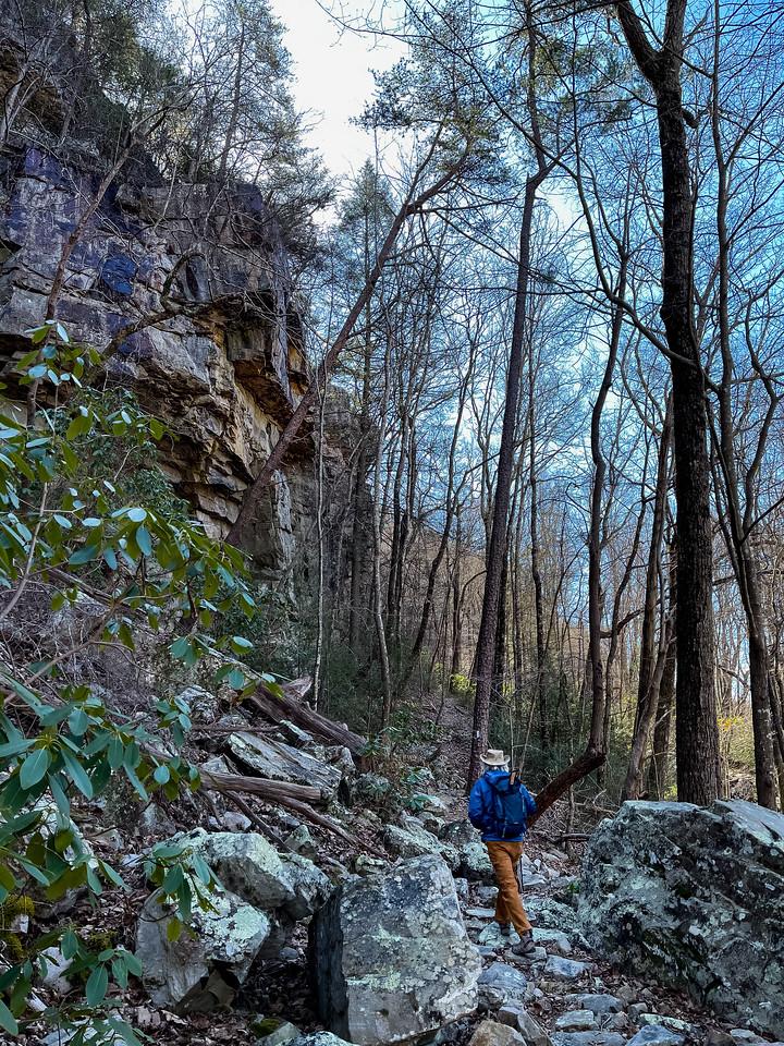 A man hiking the trail as it winds below a rocky bluff.