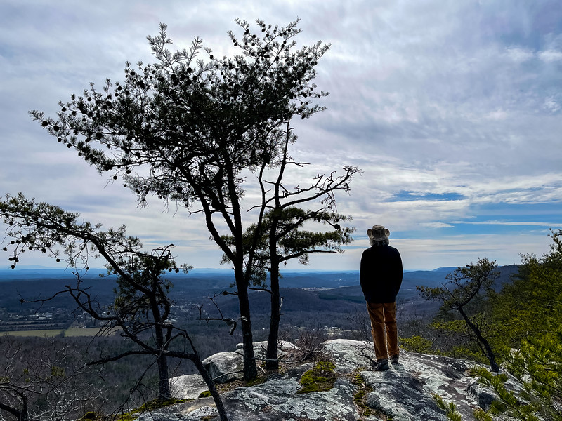 A man looking at the view of the valley and hills to the south from Cranmore Cove Overlook.