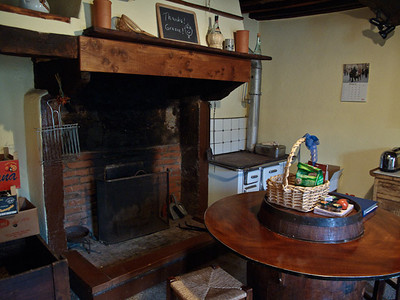 Fireplace in the kitchen and round barrel table.