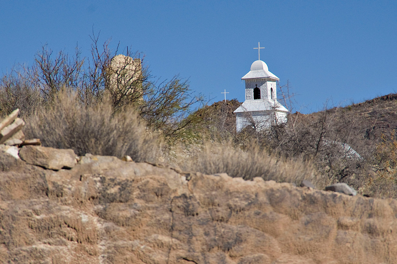 The steeple of the Sacred Heart of Jesus Catholic Church in Shafter, TX with the Shafter cross in the background.