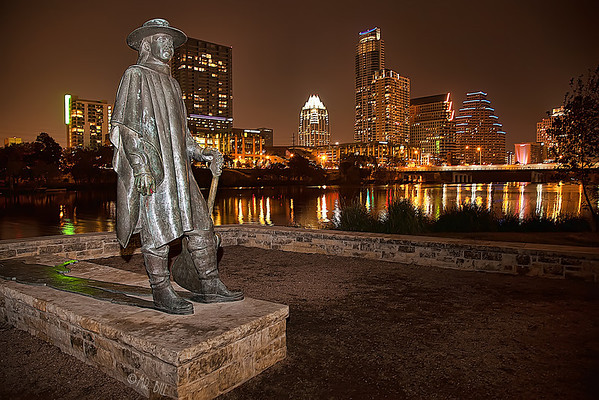 Nighttime photo of the Statue of Stevie Ray Vaughn with the Austin skyline in the background