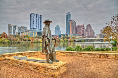 Statue of Stevie Ray Vaughn with the Austin skyline in the background