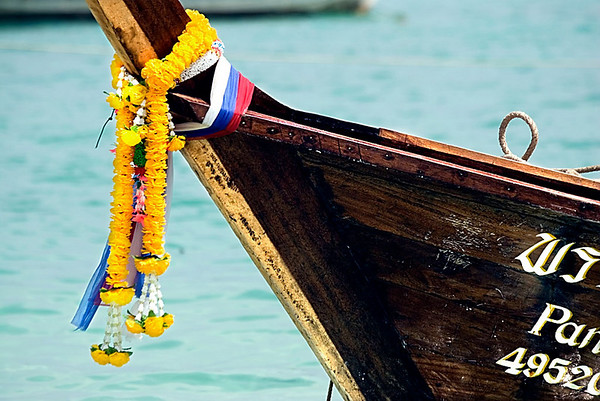 All long-tail boats (this one is in Phi Phi Islands) display colourful tassles on their bows.