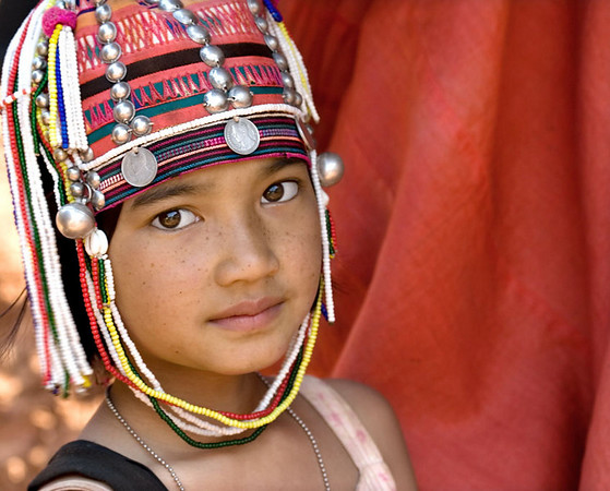 Young Akha boy in tribal headdress adorned with silver coins and baubles