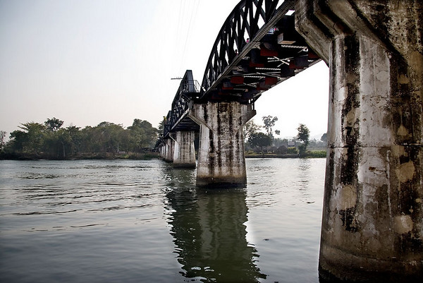 "This modern day ""Bridge on the River Kwai"" (built in 1943 and subsequently bombed by the US in 1945, which knocked out the central span), has replaced the original bridge built by the Japanese. <br /> <br /> The bridge, just to the north of Kanchanaburi town centre, was part of an enormous project , the 414km Burma-Siam Ralroad conceived by the Japanese after the Allies blocked sea routes in 1942.  It was built by 60,000 Allied prisoners and 300,000 Asian labourers under appalling conditions, including 18 hour shifts and disease."