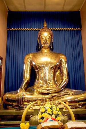 At Wat Traimit (Temple of the Golden Buddha), Bangkok, sits the solid gold Buddha which contains 5.5 ton of gold and stands 15 feet high and is 12 feet 5 inches in diameter.  It was cast in the 13th. century and is in the Sukhothai style.