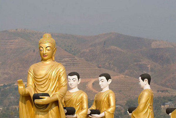 Statues of Buddha and monks just over the border in Myanmar on the outskirts of the town, Tachilek