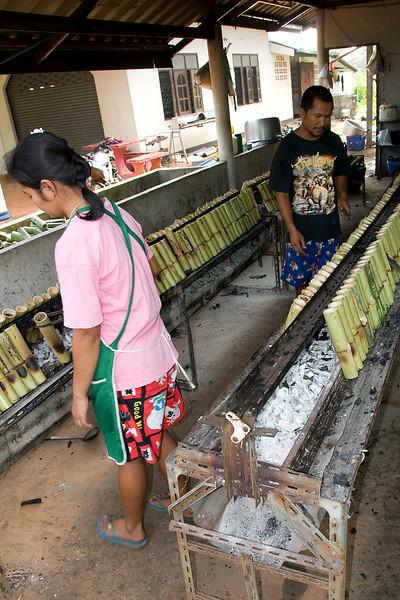 A roadside stand baking Kao Laam, sticky rice inside bamboo.