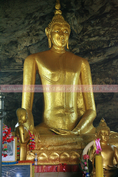 Gold Buddha inside cave near the railroad - Thailand