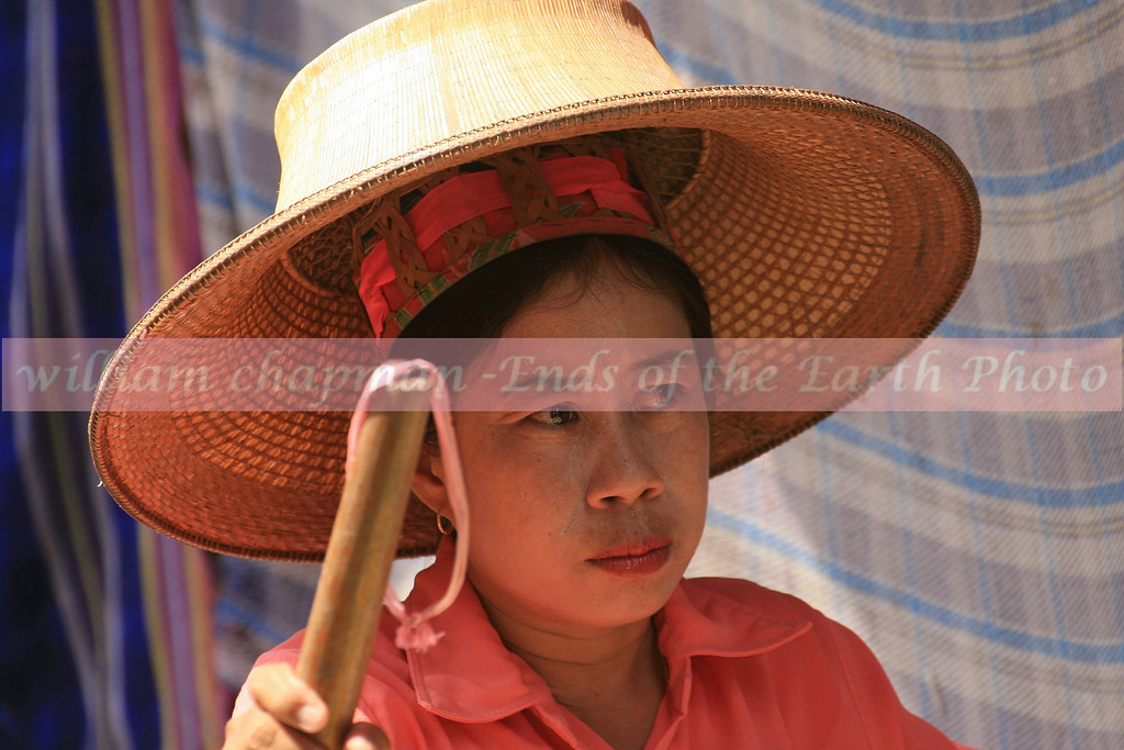 Floating market vendor with traditional Thai head gear.