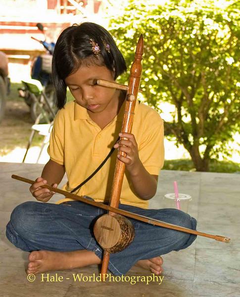 Young Female Musician Playing The Saw Sam Sai, Chiang Rai, Thailand