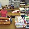"Barb Zumbiel, a member of Hopeful Lutheran Church, Florence, Ky,, sorts and folds quilts at the LWR warehouse in New Windsor, Md. She and her husband, Gary, delivered 57 quilts from their church to the warehouse and stuck around to volunteer for a few days. ""If you can tie a knot, you can make a difference,"" Barb said. Photo by Terri Lackey"