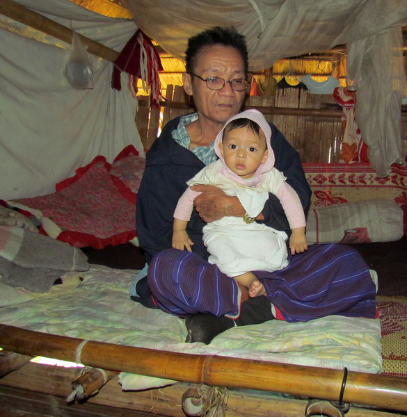 Maung Saw, grandfather to 8-month-old Ther Yu Soe, sits atop an LWR quilt in one of the houses we visited. Terri Lackey photo