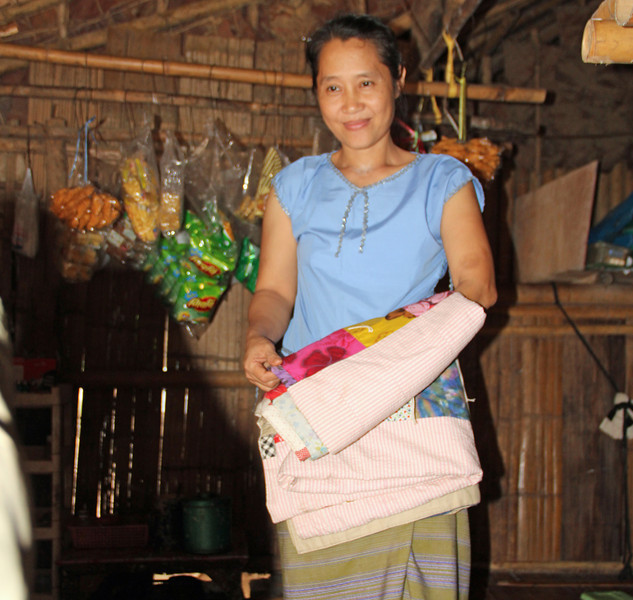 Ko Lo Wah, the newly elected chair of the Karen Women's Organization (KWO) in the Mae La refugee camp, shows off an LWR quilt owned by another resident. Photo by Melanie Gibbons