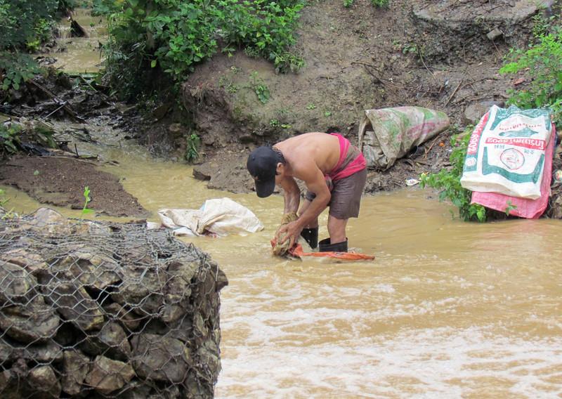 Man washing clothes in stream in Mae La refugee camp. Terri Lackey