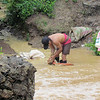 Man washing clothes in stream in Mae La refugee camp. Terri Lackey