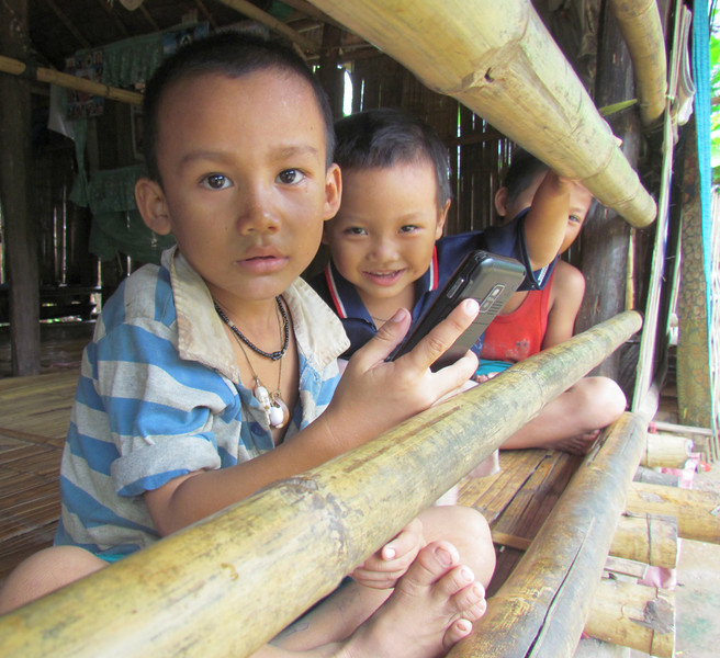 Two great-nephews of MeLe Myee play with cell phone in their home. Nine people live in their house in the Mae La refugee camp; 4 adults and 5 children. Photo by Terri Lackey