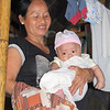 Ma Saw holds her baby, Aung, who is wearing an LWR baby kit outfit. She is also holding an LWR quilt. Melanie Gibbons