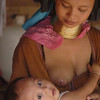 Padaung Mother Breast Feeding Her Baby in Huaysuatao, Thailand
