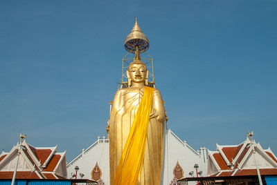 "Golden Buddha statue at Wat Intharawihan (หลวงพ่อโตวัดอินทรวิหาร), Bangkok, Thailand.   The Wat's main architectural depiction is a 32 metres (105 ft) high, 10 metres (33 ft) wide standing statue referred to as Luang Pho To or ""Phra Si Ariyamettrai"" (Maitreya). Temple dating to the 14th or 15th century, notable for its 32-meter-high gold Buddha statue. or Wat Intharavihan is a wat located in the Phra Nakhon District of Bangkok, Thailand. The temple dating to the 14th or 15th century, is notable for its 32-meter-high gold Buddha statue."