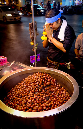 I believe these are roasting chestnuts. I don't know what brought on the vendor's prayer to Buddha, but you see that a lot.