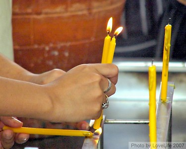 Lighting and placing prayer candles.