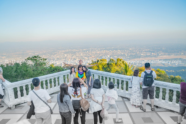 Group Asian tourists pose for photo at lookout at Wat Phra That Doi Suthep temple on mountain top.