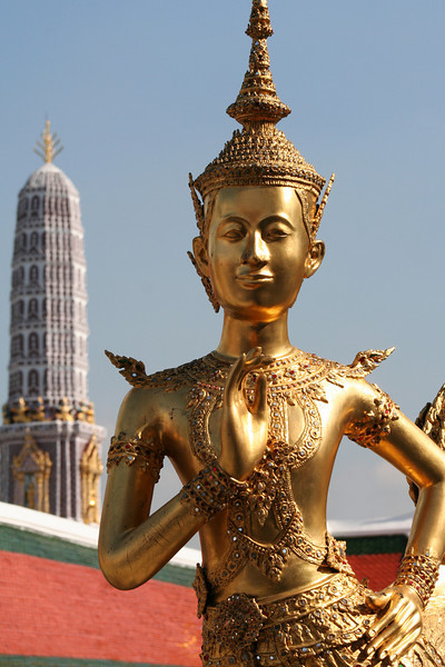 Kinnari figure, with praang in the background. Wat Phra Kaew, Bangkok.