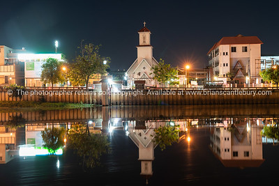 Christian church and buildings reflected in still water of Ping River at night.