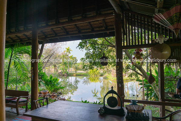 Tropical pond and garden view from cool of shady rustic style porch