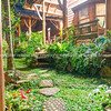 Stepping stones through lush deep green tropical garden and structure of rustic cottage.
