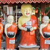 Statues of four smiling Buddhist monks holding alms containers with donation box signs